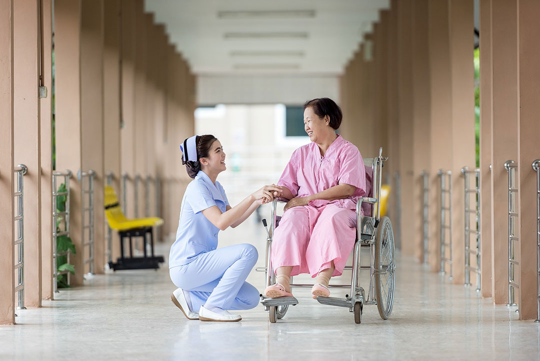 nurse helping lady in wheel chair